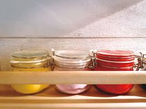 Colorful Powder in Small Glass Jars on Wooden Shelf. Close-up Colorful Powder in Small Glass Jars on Wooden Shelf Stock Photos