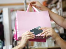 A close-up of colorful purchases and a credit card in female hands on a blurred background. Copy space. Shopping concept Stock Images