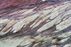 Close up of colorful rock surface, natural background, pattern and texture. Metamorphic white quartzite folded and fractured toget. Her with red coarse sandstone royalty free stock photo