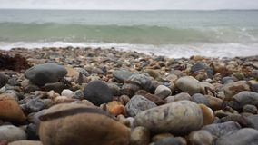 Rocky beach with ocean waves crashing on shore. Close up of colorful rocks and rounded stones blurring into distance of white turbid ocean waves crashing onto stock footage
