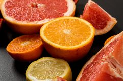Close up. Colorful slices juicy grapefruits, oranges on a black background. Ingredients royalty free stock photography
