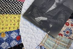 Close Up of Colorful Vintage Quilt with Antique Photo of Hands t royalty free stock photos