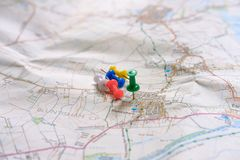 Close-up of coloured pins seen on a paper map of rural England. The cluster of pins show the objective for a cross country navigation exercise within a rural royalty free stock images