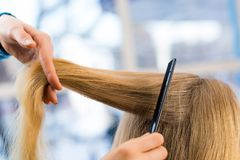 Close up combing hair. At the hairdresser Stock Photography