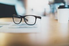 Close-up of comfortable working place in office with wooden table and glasses on it. Selective focus.Comfortable working. Place. Horizontal.Blurred background stock photo