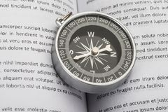 Close-up of compass on book Stock Photos