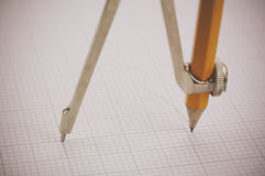 Close up of a compass on graph paper Royalty Free Stock Images