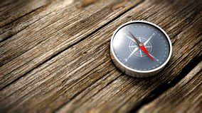 Close up compass showing north on a wooden table. Royalty Free Stock Images