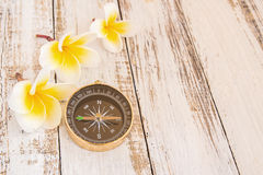 Close up compass and Tropical Plumeria flower on wooden table Stock Photos