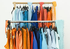 Close up on complementary colors clothes on hangers in a store. Stock Photography