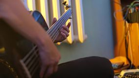 Close-up composer plays the guitar. Clamps the strings stock footage