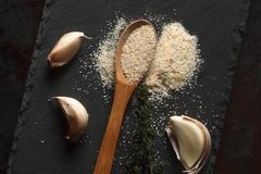 Close up composition of garlic powder, sprigs of thyme and clove. Close up composition of garlic powder sprinkled into wooden spoon, two sprigs of thyme and Stock Image