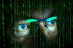 Close up of computer hacker. Eyes looking at screen with data in the foreground royalty free stock photos