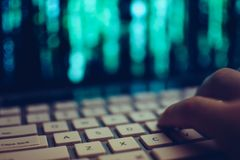 Close up of computer hacker hand on keyboard while screen showing green source code. Close up of hand on computer keyboard while screen in background shows Royalty Free Stock Photography
