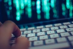 Close up of computer hacker hand on keyboard while screen showing green source code. Tilted Close up of hand operating computer keyboard while screen in Stock Photography