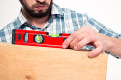 Close up of concenrated bearded young man using spirit level. Close up of concenrated bearded young man in plaid shirt using spirit level over white background Royalty Free Stock Photo
