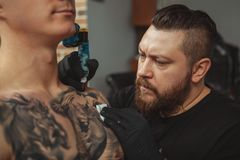 Bearded tattooist making tattoos on body of his client. Close up of a concentrated bearded tattoo artist working, tattooing shoulder of a male client royalty free stock images