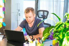 Close up concentrated young caucasian man in casual clothes working on laptop while sitting at his working place in office. Concen stock photography
