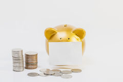 Conceptual image, pile of coins close gold piggy bank on white background. Stock Images