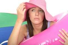 Close Up of a Concerned Anxious Unhappy Young Woman On Holiday. Close up of a concerned anxious unhappy Young Woman in Her Twenties On Holiday wearing pink hat Royalty Free Stock Photo