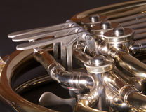 Close up of a concernt french horn. Close up of a concert french horn, set against a dark background Stock Photos