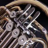 Close up of a concert french horn. Close up of the keys and valves of a concert french horn set against a dark background Royalty Free Stock Photography