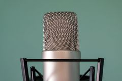 Close-up of a condenser studio microphone with a shock absorber on a blue background. The concept of high-quality professional stock image
