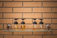 Close up conditioning shampoo and shower cream bottles put on glass shelf with brick wall in the background beside swimming pool. stock image