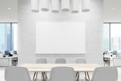 Close up of a conference room table, white, poster. Close up of a wooden table in a meeting room of an office with a white wall, an open office area in the Royalty Free Stock Photo