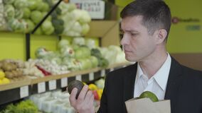 Close-up of confident adult Caucasian man choosing pomelo in grocery, putting citrus fruits into pack and leaving