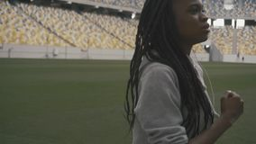Close-up of confident african american teenage girl listening music and jogging on the urban stadium background stock footage