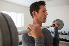Close up of confident athelte lifting barbell at gym Stock Images