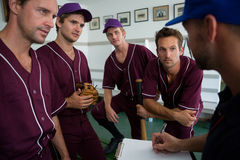 Close up of confident baseball team planning with coach. While standing at locker room stock photo