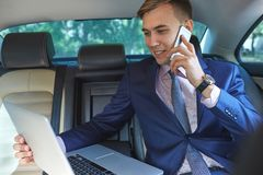 Confident businessman talking on mobile phone sitting in the back seat of a car. Close-up of confident businessman, in blue suit, talking on mobile phone Stock Photos