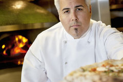 Close-up of a confident chef with pizza Stock Photography
