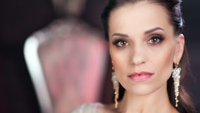 Close-up confident face of beautiful European woman with amazing evening makeup and perfect skin. Looking at camera. Portrait of pensive adorable fashionable stock video footage