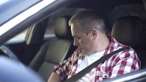 Close-up of confident middle aged Caucasian man fastening seat belt sitting on driver's seat and turning on engine