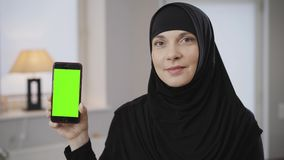 Close-up of confident muslim woman in black hijab holding smartphone with green screen. Modern beautiful lady in black