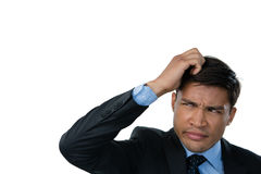 Close up of confused businessman with hand in hair. Against white background Stock Photography