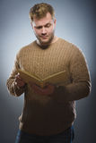 Close-up of confused man reading book against gray background Stock Image