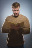 Close-up of confused man reading book against gray background Royalty Free Stock Photography