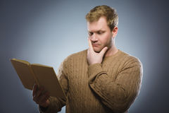 Close-up of confused man reading book against gray background Royalty Free Stock Image