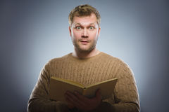 Close-up of confused man reading book against gray background Royalty Free Stock Photos