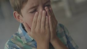 Close-up of confused scared boy standing in the smoky room coughing and covering face with his hands. Concept of danger. Close-up of a confused scared boy stock video footage