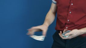 Close up conjurer in red shirt perform playing cards magic tricks. Blue background stock footage