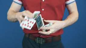 Close up conjurer in red shirt shuffle playing cards, show Queen of Spades stock footage