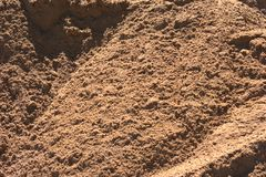 Close up of construction sand with furrows and large clumps of sand visible. Close up of construction sand with large clumps of sand visible and laying over each Royalty Free Stock Image