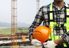 Close up construction worker holding helmet. Close-up construction worker holding helmet, construction safety concept royalty free stock photos