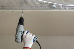 Close-up of constructor worker hand in protective glove with electrical cordless screwdriver connecting suspended drywall ceiling stock image