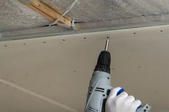 Close-up of constructor worker hand in protective glove with electrical cordless screwdriver connecting suspended drywall ceiling stock photos